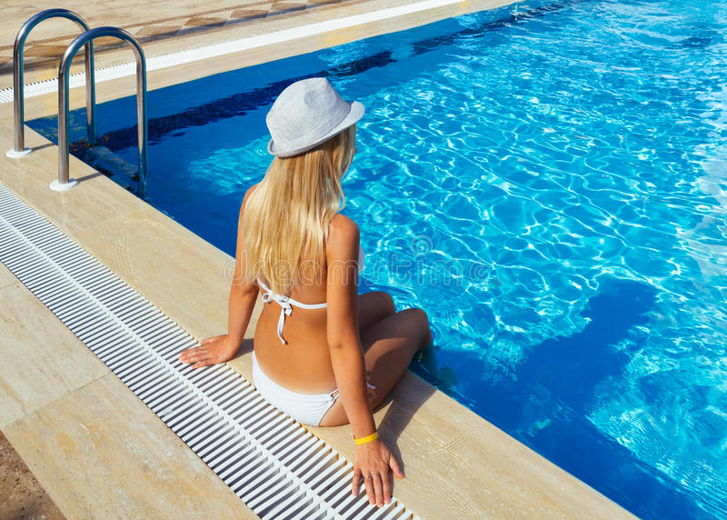 Blonde girl sitting by the pool stock image