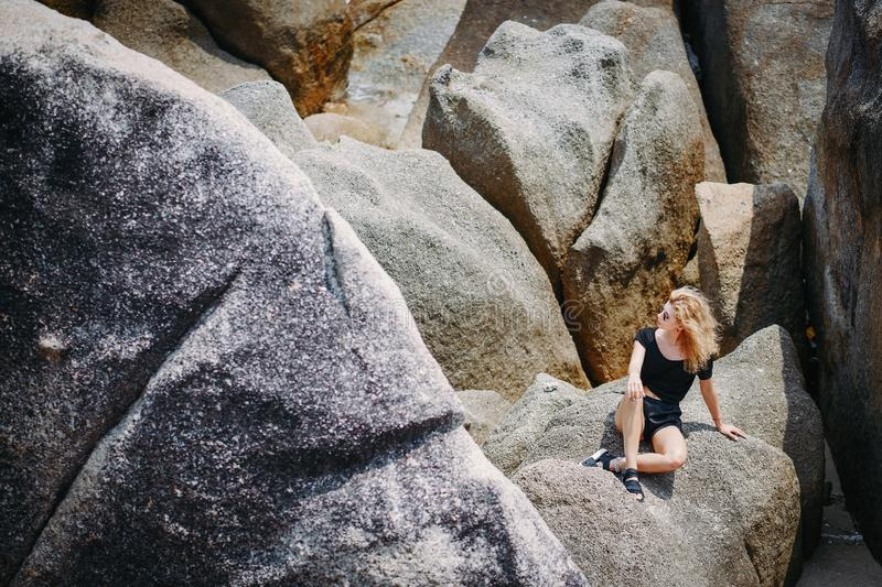 Blonde girl sitting on a rock formation royalty free stock photos