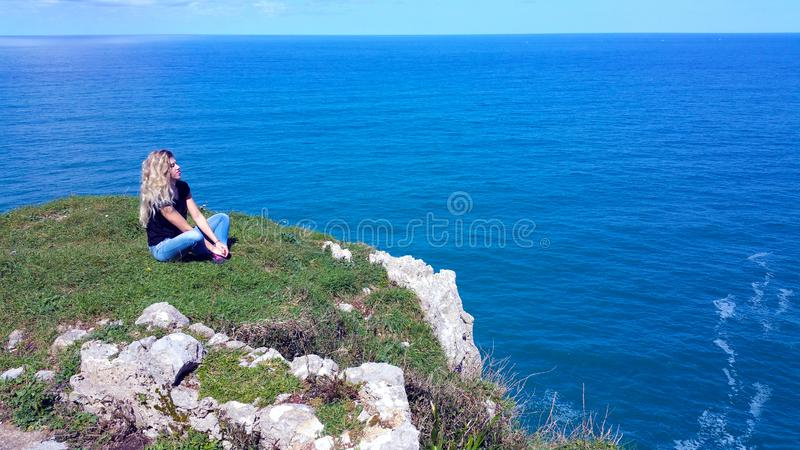 Blonde girl sitting on the rock, looking on the water stock image