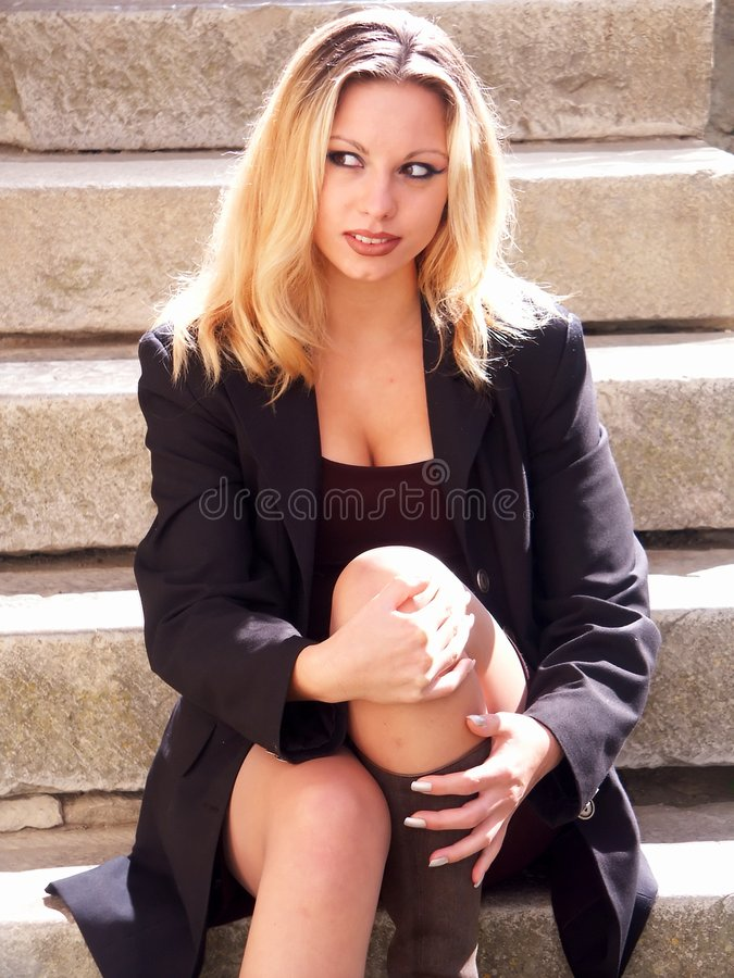 Blonde girl sitting on stairs stock photo