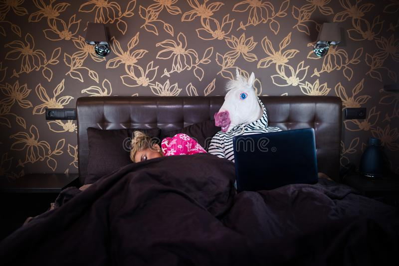 Blonde girl sleeping with funny man in comical mask. Unusual couple royalty free stock images