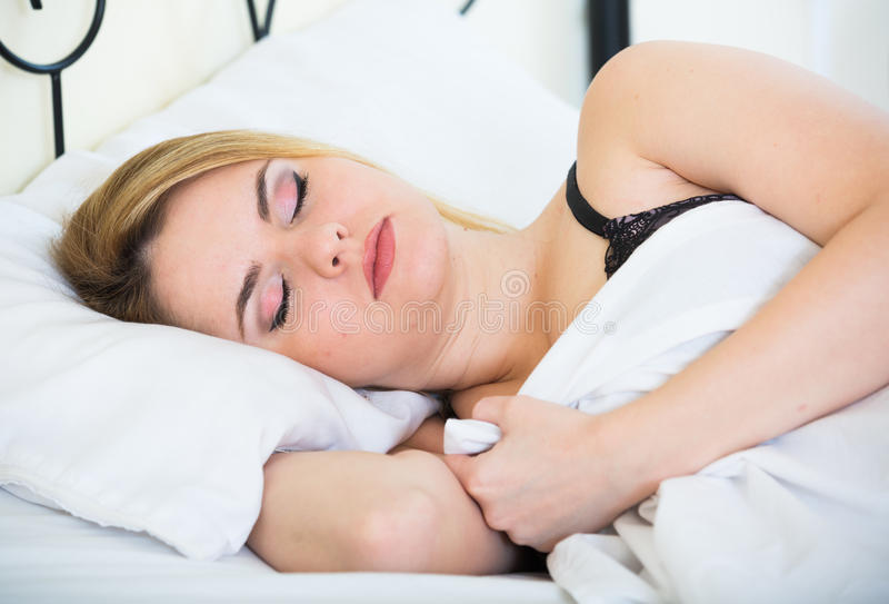 Blonde girl sleeping on white pillow in bed at home. Beautiful young blondie sleeping in bed at home royalty free stock photo