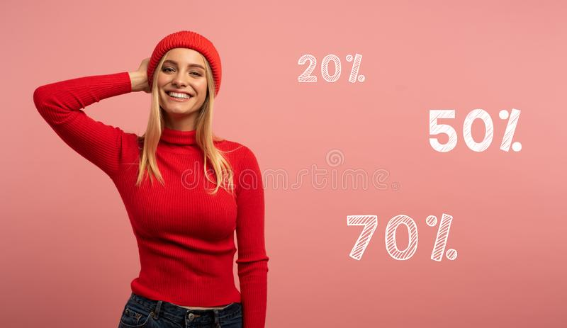 Blonde girl smiles with red hat and cardigan. Pink background for blank space for your discount text royalty free stock photography