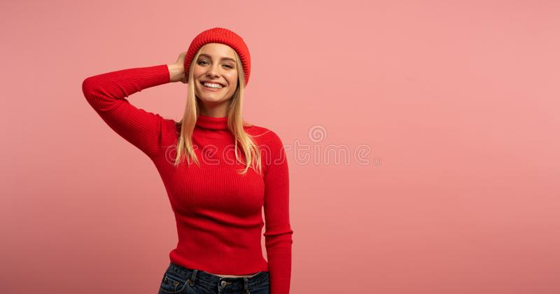 Blonde girl smiles with red hat and cardigan. Pink background for blank space for your text royalty free stock photos