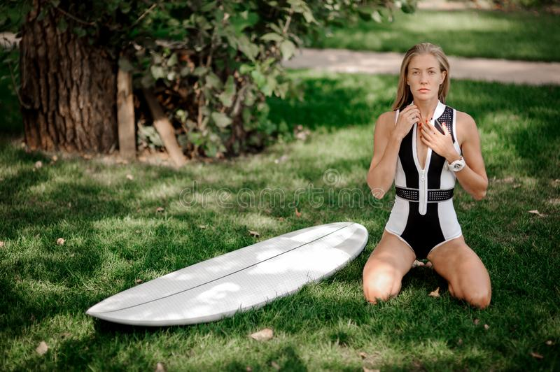 Blonde girl standing on her knees near the wakeboard. Rear view blonde girl in black and white swimsuit standing on her knees near the wakeboard on the blurred stock photo
