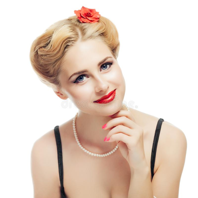 Blonde girl style pin-up in black dress and pearl necklace looks playfully at camera and gently touching face with your stock photo
