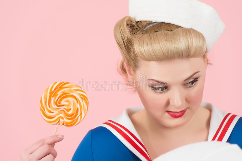 Blonde girl and sweet lollipop. Close up of candy woman on pink background royalty free stock photography