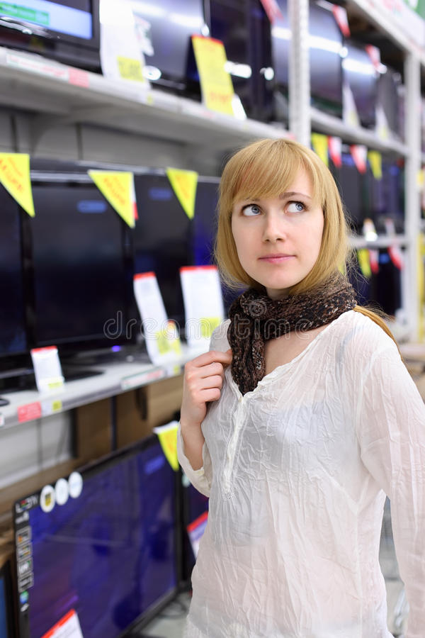 Blonde girl thinks about buying TV in supermarket royalty free stock image