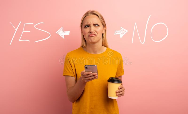 Blonde girl thinks about the right option. Yes or no. Confused and pensive expression. Pink background stock photo