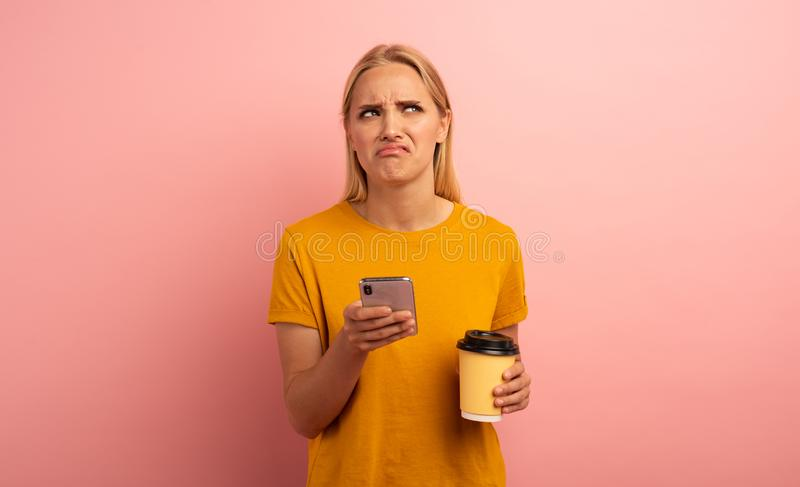 Blonde girl thinks about the right option. Yes or no. Confused and pensive expression. Pink background. Blonde girl thinks about the right option with her royalty free stock photos