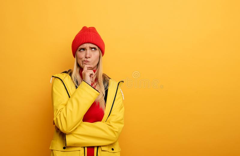 Girl thinks about something. Confused and pensive expression. Yellow background stock photos