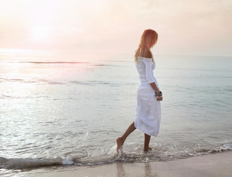 Blonde girl walking by the sea in the sunset royalty free stock image