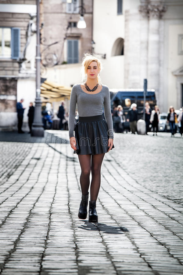 Blonde girl walking on the street in the city wearing a skirt. royalty free stock image
