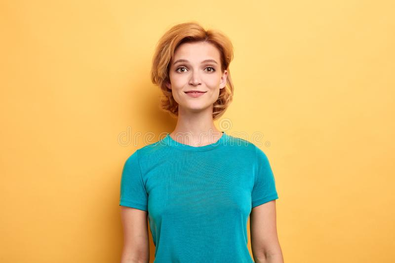 Blonde girl wearing blue stylish T-shirt and looking at the camera royalty free stock photo
