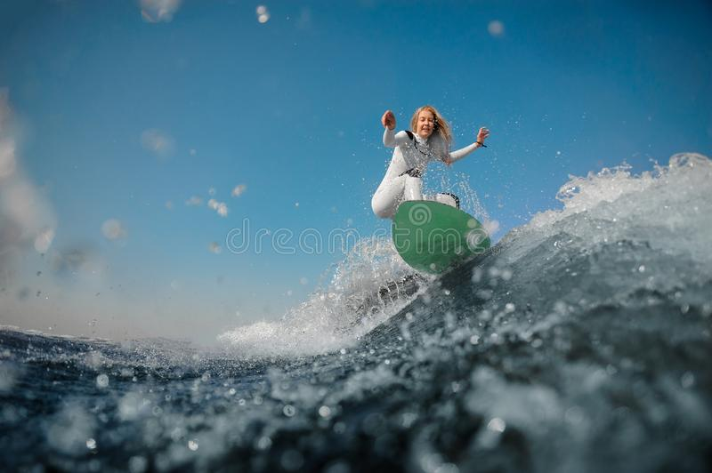 Blonde girl in white swimsuit jumping on the green wakeboard. Beautiful blonde girl in the white sport swimsuit riding on the green wakeboard on the bending royalty free stock images