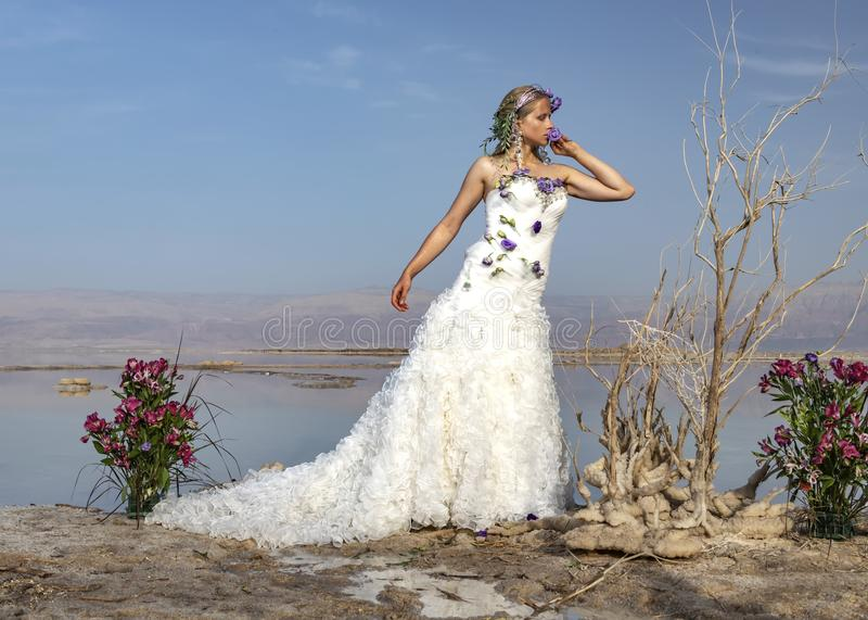 Blonde girl in a white wedding dress standing on a salt formation of the Dead Sea royalty free stock image