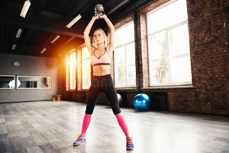 Blonde girl working out at the gym with a kettlebell. crossfit exercise stock images
