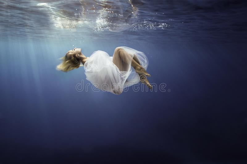 Blonde girl wrapped in fine white cloth, sank in blue deep water of ocean, against dark sea background. royalty free stock photo