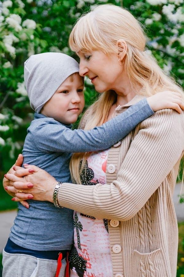 Blonde glückliche junge Großmutter, die Kind von fünf Jahren umarmt lizenzfreie stockfotografie