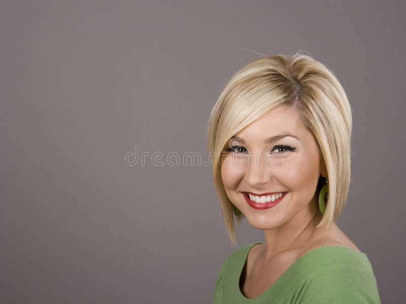 Blonde in Green Dazzling Smile royalty free stock photo