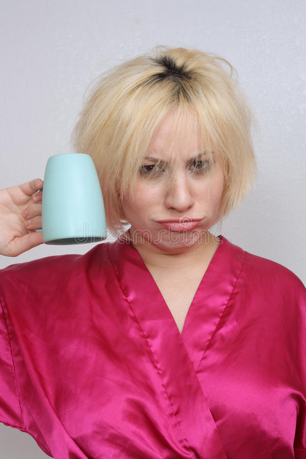Blonde Grouchy con una tazza di caffè vuota immagini stock