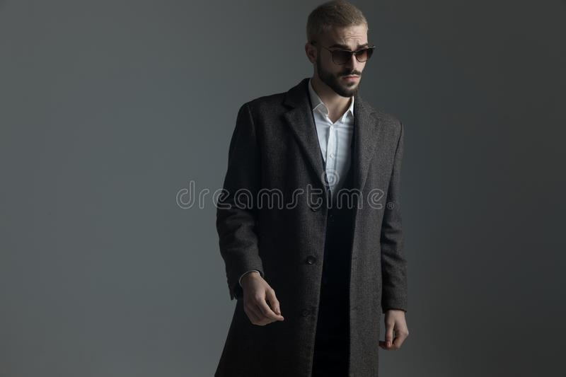 Blonde guy in suit with sunglasses and longcoat warlking stock image