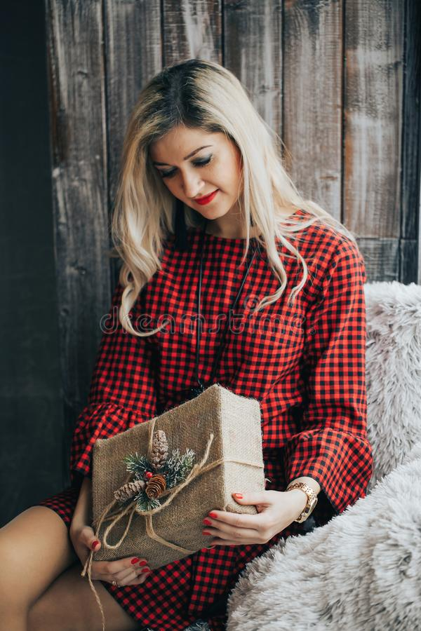 Blonde hair beautiful woman with present in her hands. Young woman portrait hold gift in christmas color style royalty free stock photography