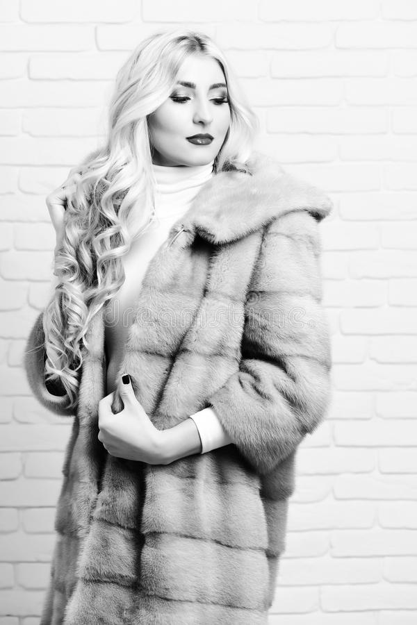Blonde hair in waist coat of grey fur and fashion makeup on brick wall studio background. fashionable woman in fur royalty free stock photography