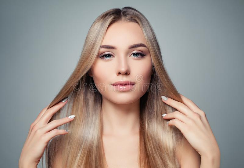Blonde hair woman. Beautiful model girl with long straight healthy hairstyle. Haircare, hair styling and hair straightener concept.  stock photos