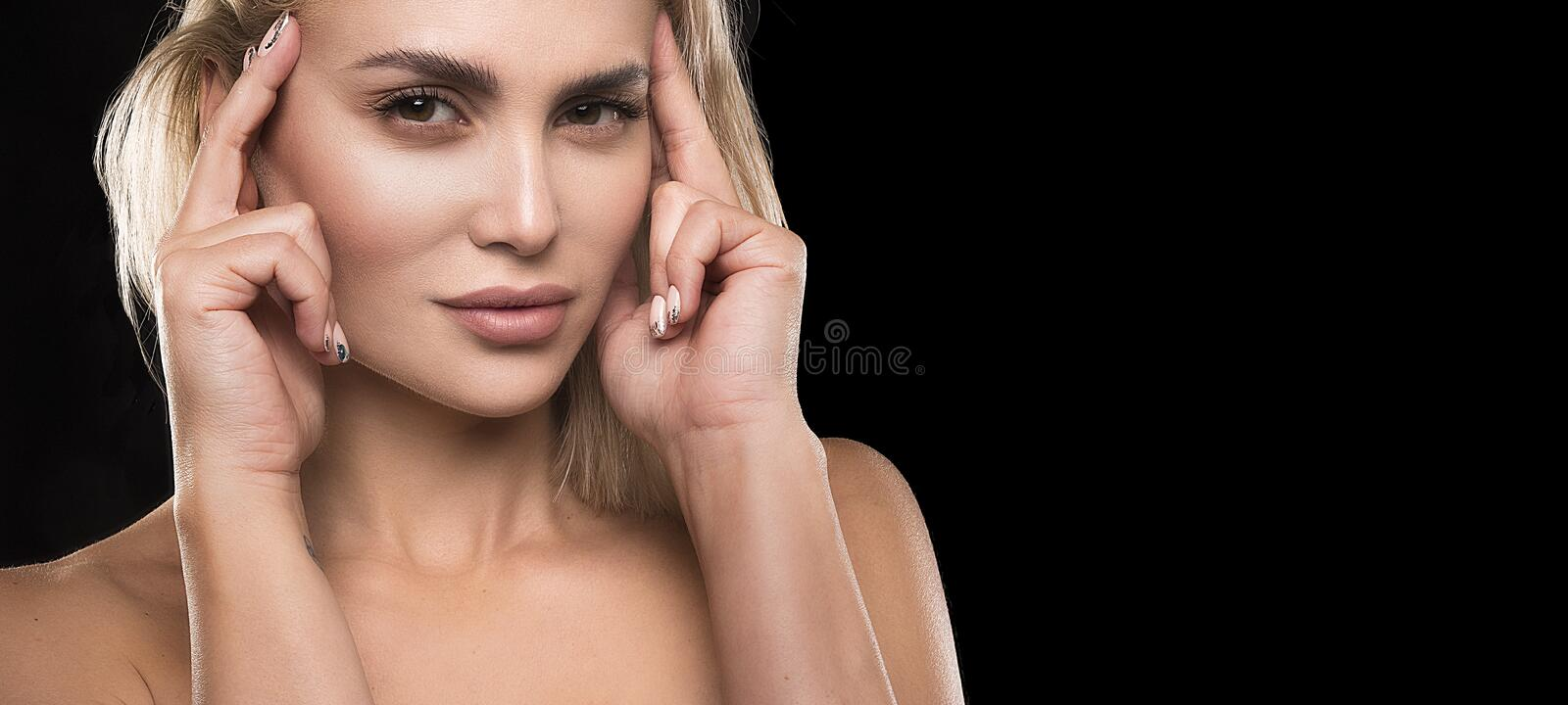 Blonde hair woman with beauty face skin over dark background female portrait.  royalty free stock image