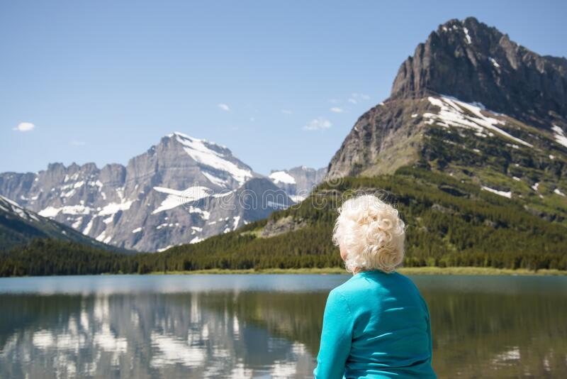 Blonde hair woman looking at the mountain landscape of Montana. 70 year old tourist looking at beautiful mountains of Glacier royalty free stock photos