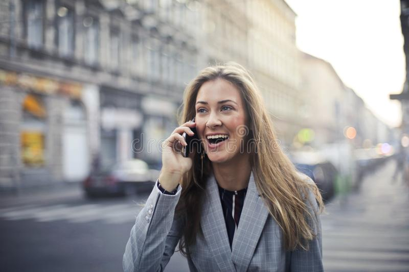 Blonde Hair Woman Wearing Gray Suit Jacket Holding Smartphone stock photo