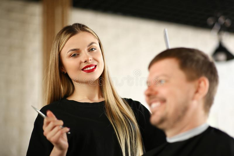 Blonde Hairdresser with Man Customer in Salon royalty free stock photo