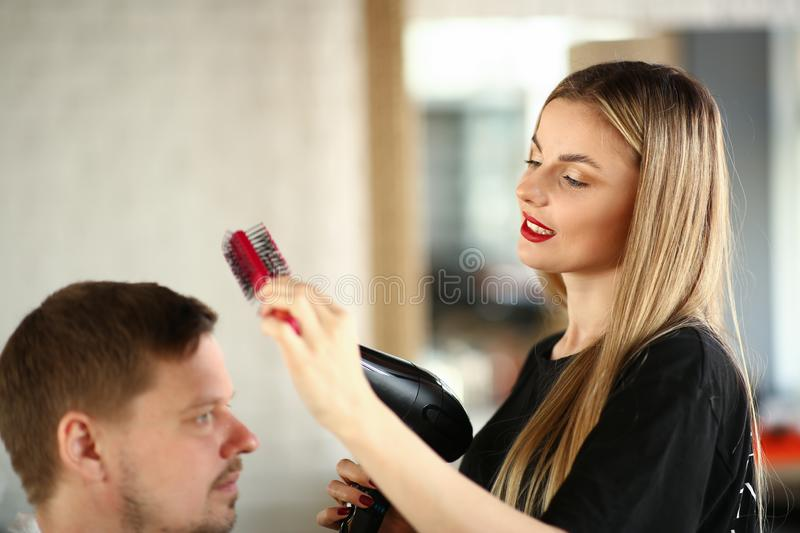 Blonde Hairdresser Using Hairbrush for Hairstyle royalty free stock images