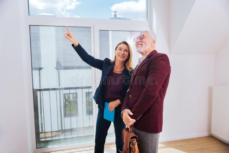 Blonde-haired aantrekkelijke landgoedagent die aardig groot venster in modern huis tonen stock afbeeldingen
