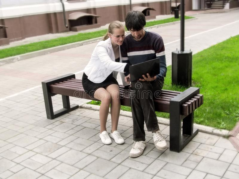 Blonde-haired adult girl in glasses, smiling, shows something on the laptop to a dark-haired man, sitting on a bench. People. Working outside the office royalty free stock images