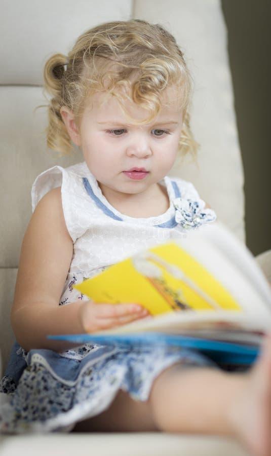 Blonde Haired Blue Eyed Little Girl Reading Her Book. Adorable Blonde Haired Blue Eyed Little Girl Reading Her Book in the Chair royalty free stock image