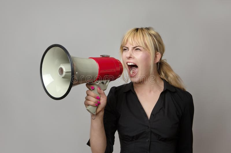 What have you got to shout about. Blonde haired business woman shouting into a bullhorn royalty free stock image
