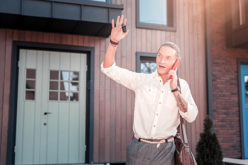 Blonde-haired businessman lifting his hand saying bye to his family. Saying bye. Blonde-haired businessman lifting his hand saying bye to his family while going stock photos