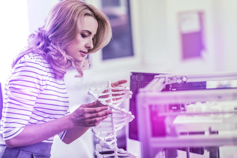 Blonde-haired experienced chemist looking at the model of molecular chain stock photos