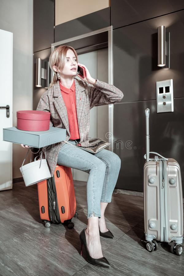 Blonde-haired girlfriend holding boxes calling the taxi. Calling the taxi. Blonde-haired girlfriend holding boxes calling the taxi while sitting on suitcase stock image