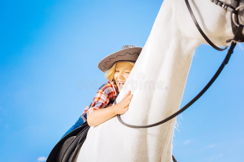 Blonde-haired grappig meisje die terwijl het berijden van haar wit paard lachen stock afbeelding