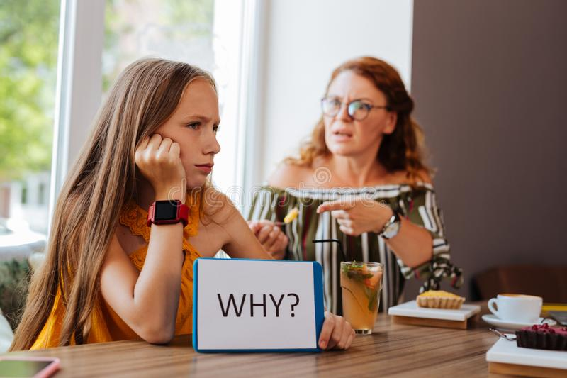 Blonde-haired meisje die met haar bezige moeder debatteren royalty-vrije stock afbeelding