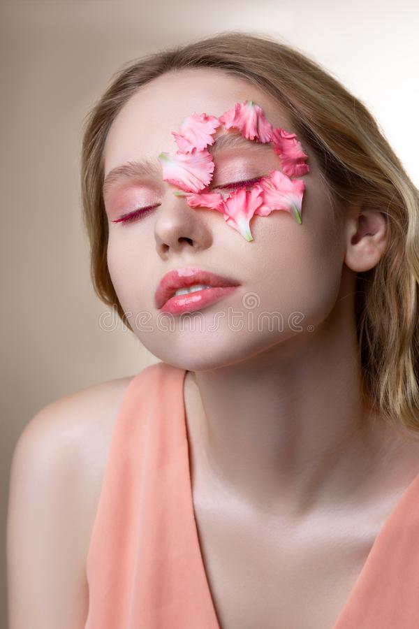 Blonde-haired model wearing pink dress having pink eyeshades. Pink color. Blonde-haired model wearing pink dress having pink eyeshades showing little pink petals royalty free stock images