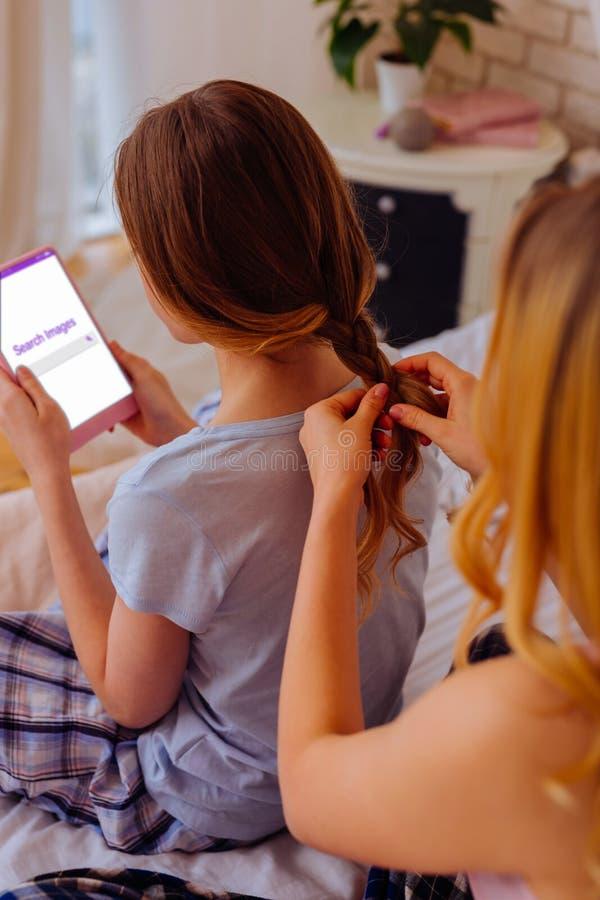 Blonde-haired oudere zuster bindende vlecht voor haar tiener stock fotografie