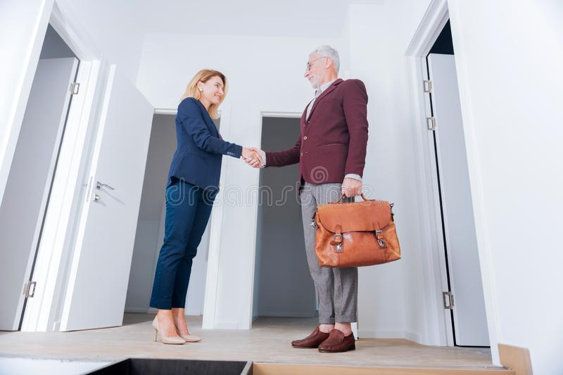 Blonde-haired real estate broker shaking hand of her rich influential client. Shaking hand. Blonde-haired real estate broker wearing elegant costume shaking hand stock image