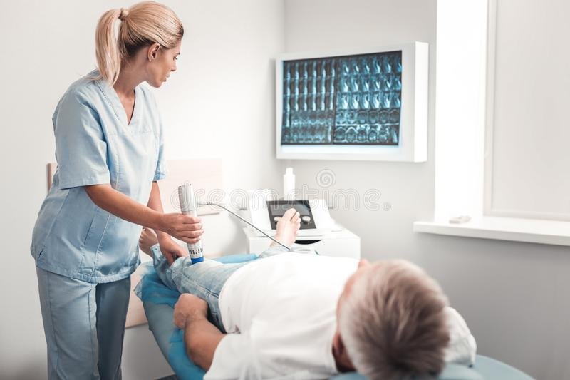 Blonde-haired smart medical assistant examining knee. Smart assistant. Blonde-haired smart medical assistant wearing blue uniform examining knee of retired man royalty free stock images