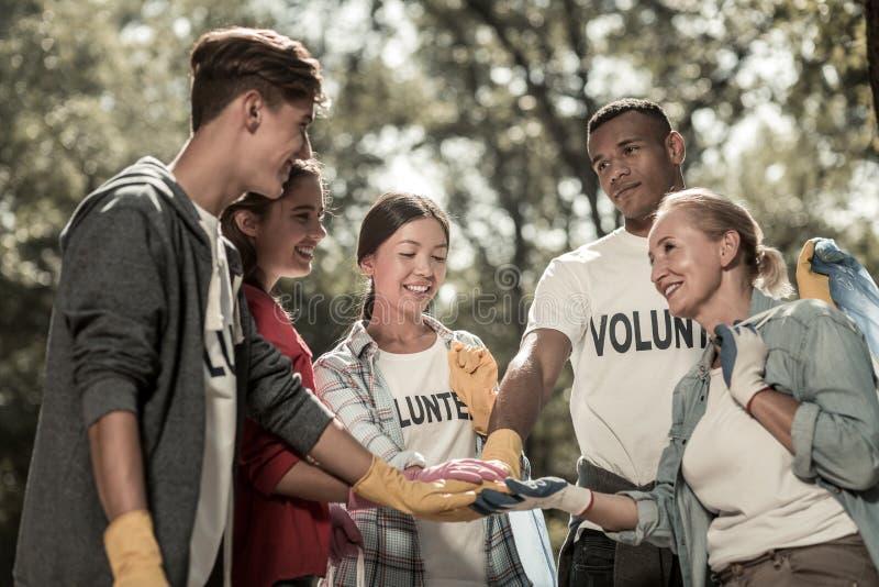 Blonde-haired teamleider van jonge vrijwilligers die het proces van het werk organiseren stock afbeelding