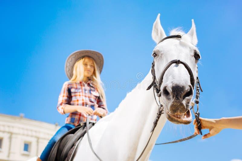 Blonde-haired tiener die van haar paardrijdenles genieten royalty-vrije stock fotografie
