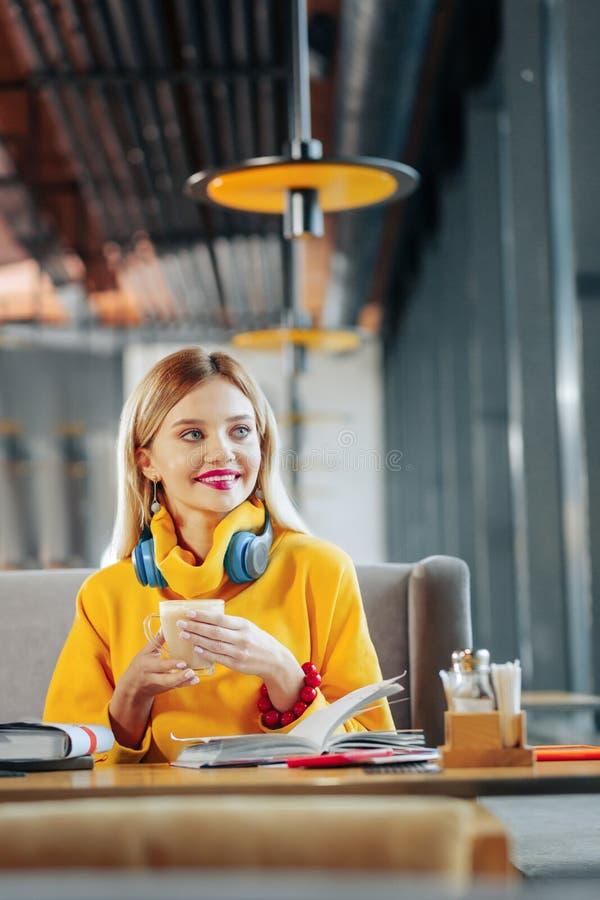 Blonde-haired vrouw die heldere gele sweater het drinken koffie dragen royalty-vrije stock afbeeldingen